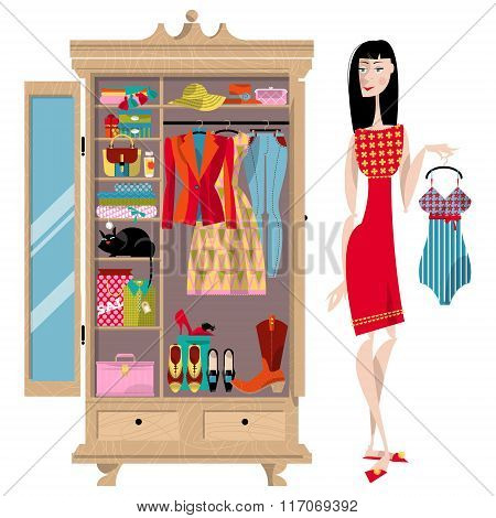 Woman Standing Near An Open Wardrobe. Closet With Clothes, Bags, Boxes And Shoes. Shopping Time.