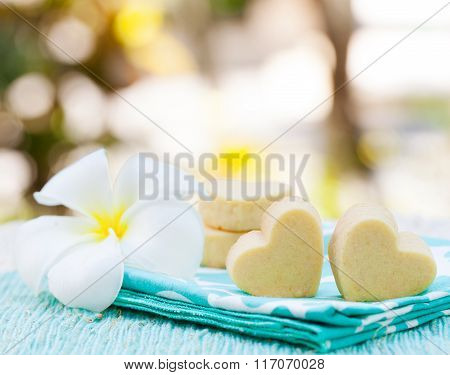 Handmade heart shape cookies on wooden plate and blue napkin Outdoor background Frangipani flower