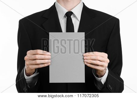 Business And Advertising Topic: Man In Black Suit Holding A Gray Blank Card In Hand Isolated On Whit