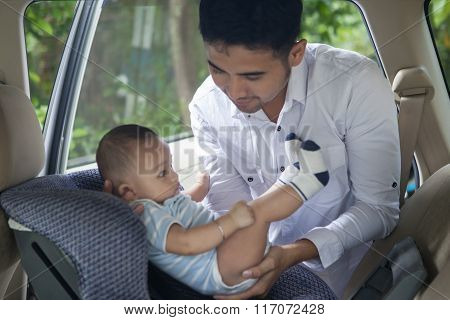 Father Lifting His Baby From The Car Seat