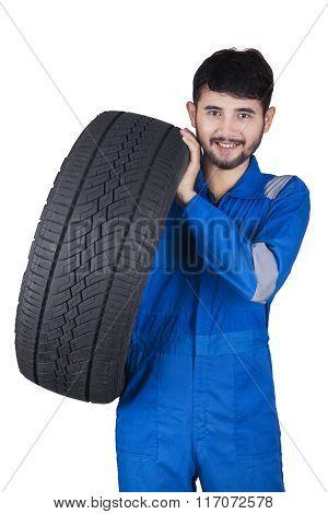 Handsome Mechanic Lifting Tire In Studio