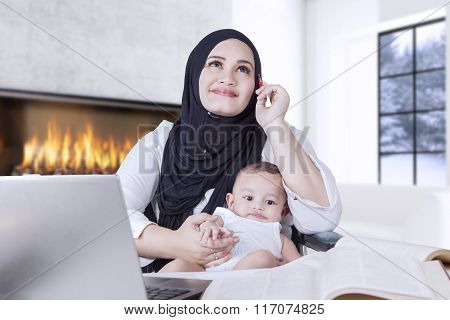 Mother Holding Her Baby While Thinking