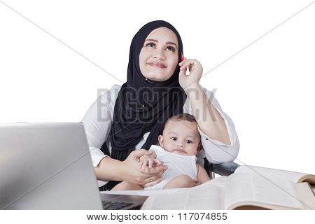 Mother Working While Nursing Baby