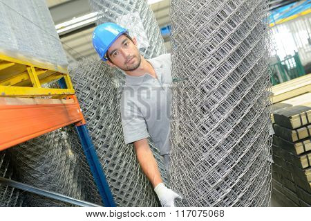 Man holding roll of metal fencing wire