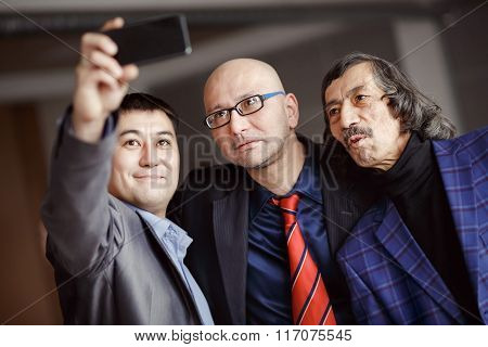 Businessmen In Suits Doing Selfie Indoors, Mature. Business Team Of Three People. Modern Technology
