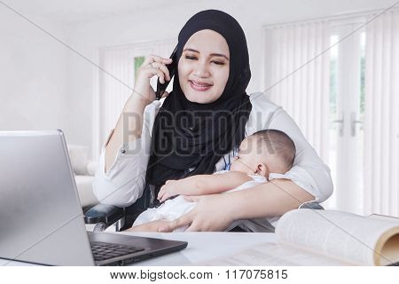 Young Mother Nursing Her Baby While Working