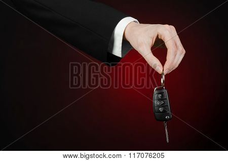 Business And Gift Theme: Car Salesman In A Black Suit Holds The Keys To A New Car On A Dark Red Back