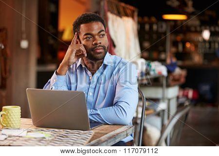 Male Fashion Designer Working At Laptop In Studio