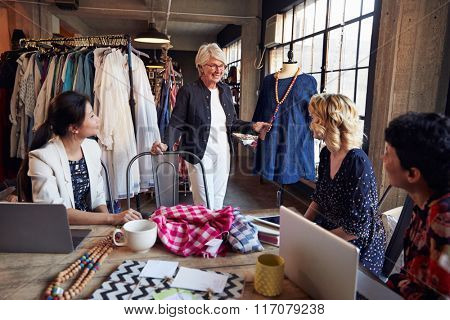 Four Fashion Designers In Meeting Discussing Garment