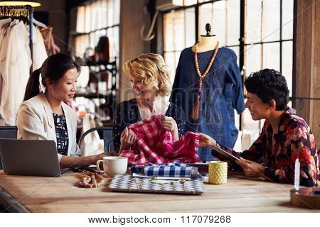 Three Fashion Designers In Meeting Discussing Textiles