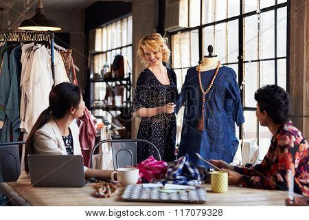 Three Fashion Designers In Meeting Discussing Garment