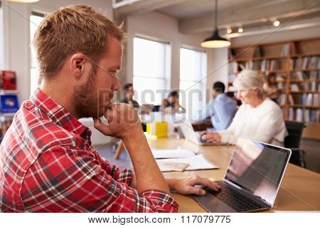 Businessman Using Laptop At Desk In Busy Office