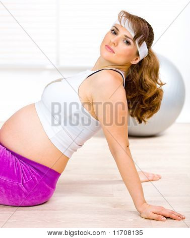 Smiling beautiful pregnant woman sitting on floor at home and relaxing after exercising