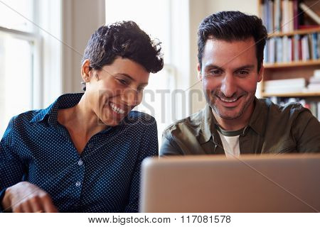 Two Businesspeople Working At Laptop In Office