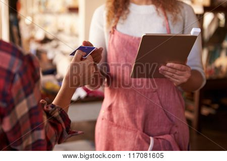 Sales Assistant With Credit Card Reader On Digital Tablet