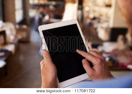 Close Up Of Man Using Digital Tablet In Shop