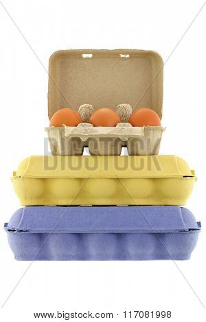Paper pulp egg tray packages made of recycled paper in different sizes and colors full of fresh chicken eggs isolated on white
