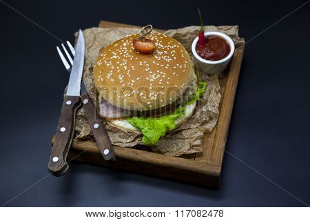 Classical American fresh juicy burger with chicken and ham on a wooden tray with a spicy chili sauce. Beautiful photo on a dark background.