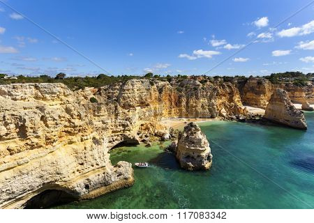Boat with tourists visiting the caves near the beach ( praia da Marinha ), Algarve