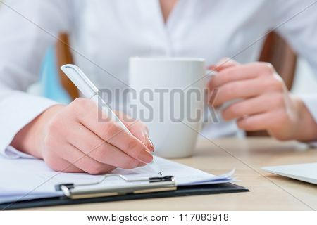Pleasant female office worker making notes