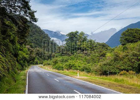 Scenic winding road through temperate rainforest at the South Island of New Zealand