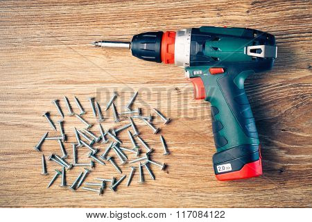 screws fasteners and electric screwdriver on wooden background