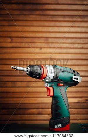 cordless screwdriver against wooden background with copyspace