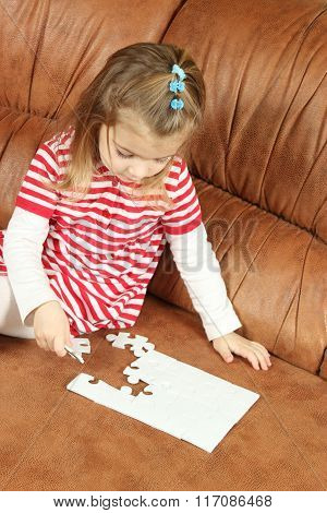 Little Girl Playing With Puzzle Pieces