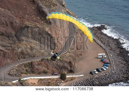 Breathtaking view of an unidentified pilot flying with a paraglider