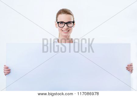 Cheerful woman holding white board
