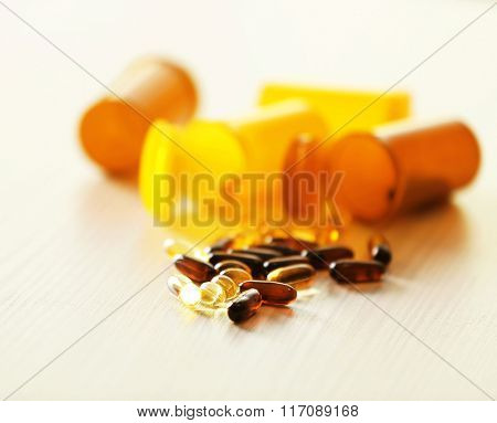 Different capsules spilled from orange pill bottles on wooden table, close up
