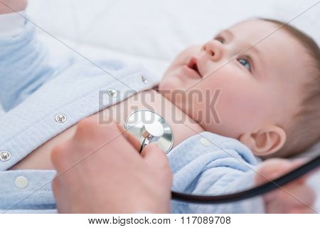 Professional pediatrician examining infant