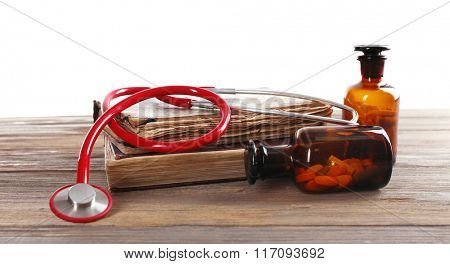 Books, pills and stethoscope on white background