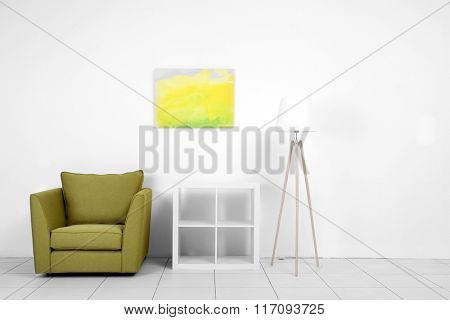 Living room interior with green armchair, white shelf and lamp on white wall background