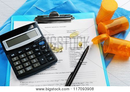 Medical stethoscope, clipboard, pills and calculator, on blue background