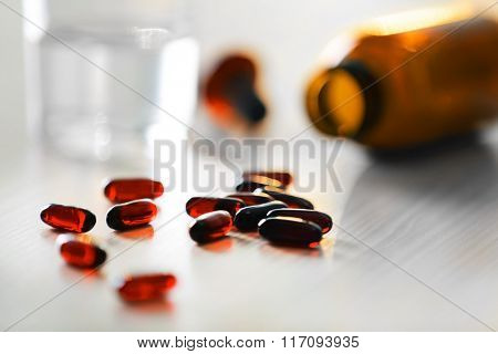 Brown capsules spilled from pill bottle and glass of water on wooden table, close up