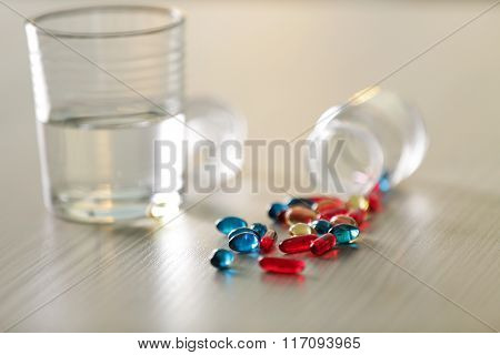 Pile of blue and red capsules with glass of water on the table, close up