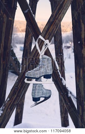 Ice skates hanging on rustic wooden pole, winter landscape background. Retro filter effect.