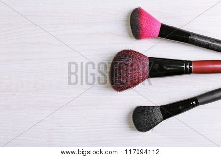 Makeup tools on a wooden background