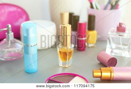 Perfume bottle with makeup tools and cosmetics on a table