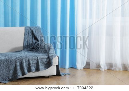 Sofa in the room in front of the window with curtains