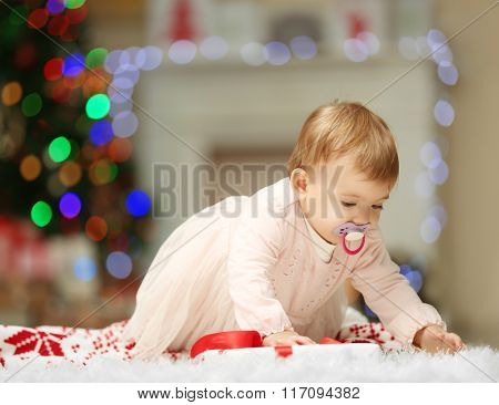 Sweet baby girl with a soother crawling on Christmas background
