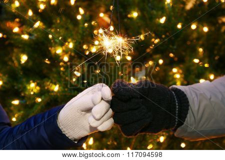 Couple holding Bengal lights on Christmas background