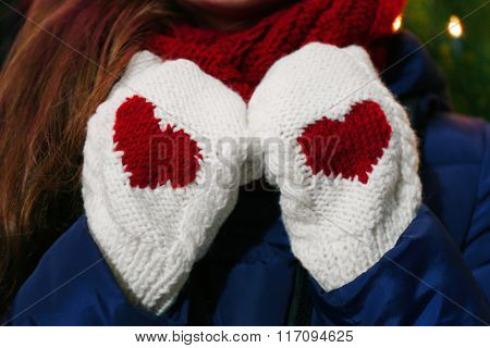 Female hands in warm white gloves with red heart