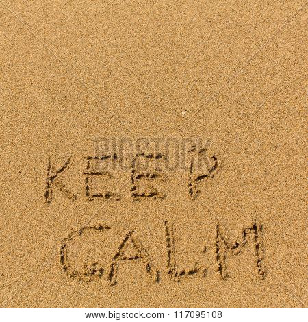 Keep calm - text written on sandy beach. Background, texture of the sand.