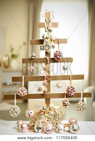 A handmade Christmas tree and baubles on the table in the room