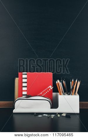 School supplies near blackboard, close up