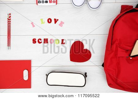 School set with backpack, heart and supplies on light wooden background