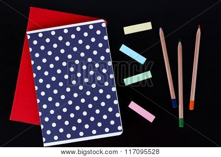 Notebooks with coloured pencils and stickers on black table