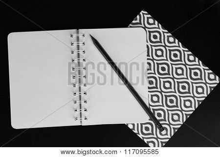 Notebooks with stickers and pencil on black table